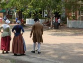 Costumed interpreters mingle with visitors to teach the history of Colonial Williamsburg